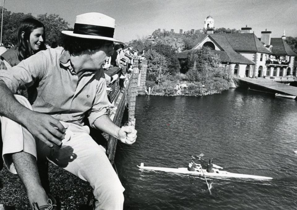 Oct. 22, 1978: Malcolm Logan cheered boats on from the Larz Anderson Bridge. The Weld Boathouse can be seen to the right. This boathouse is home to Harvard's rowing, boating, and crew teams.